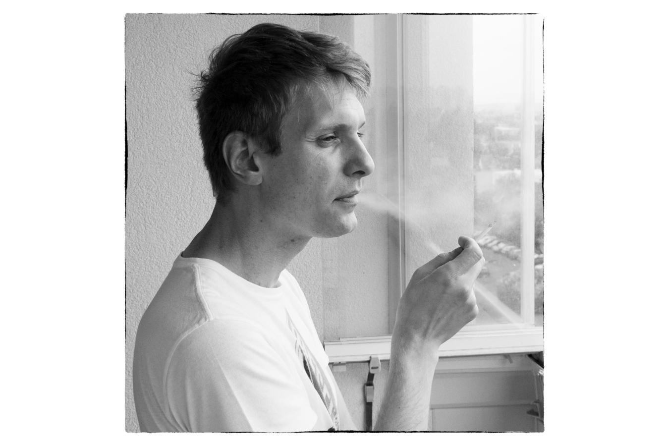 Motiv na fotografii je jednoznačný. Jedná se o portrét muže kouřícího cigaretu. Fotografie čitelně zasazuje fotografovaného do prostředí, ale neobsahuje žádné zbytečné detaily, které nemají pro hlavní motiv význam a mohly by být rušivé.jpg