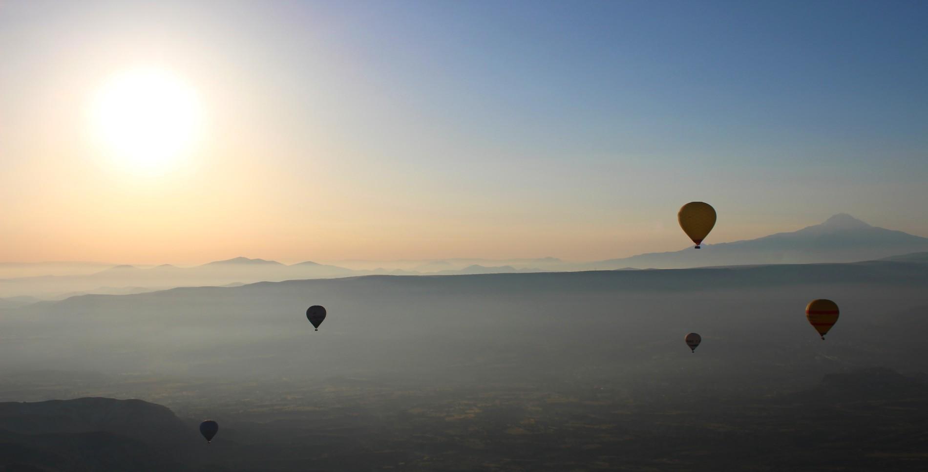 Balóny nad Kapadokií. Jeden z mnoha snímků pořízených v protisvětle. Foceno ve výšce 530 metrů nad zemí (1 675 m n. m.), v pozadí na snímku je 3 917 metrů vysoká vyhaslá sopka Erciyes Dağı. Canon EOS 100D, objektiv EF-S 18-55, 1/200 s, F10, ISO 1000, ohnisko (EQ35) 38 mm. Vyfoceno 10. června v 6.02 místního času.jpg