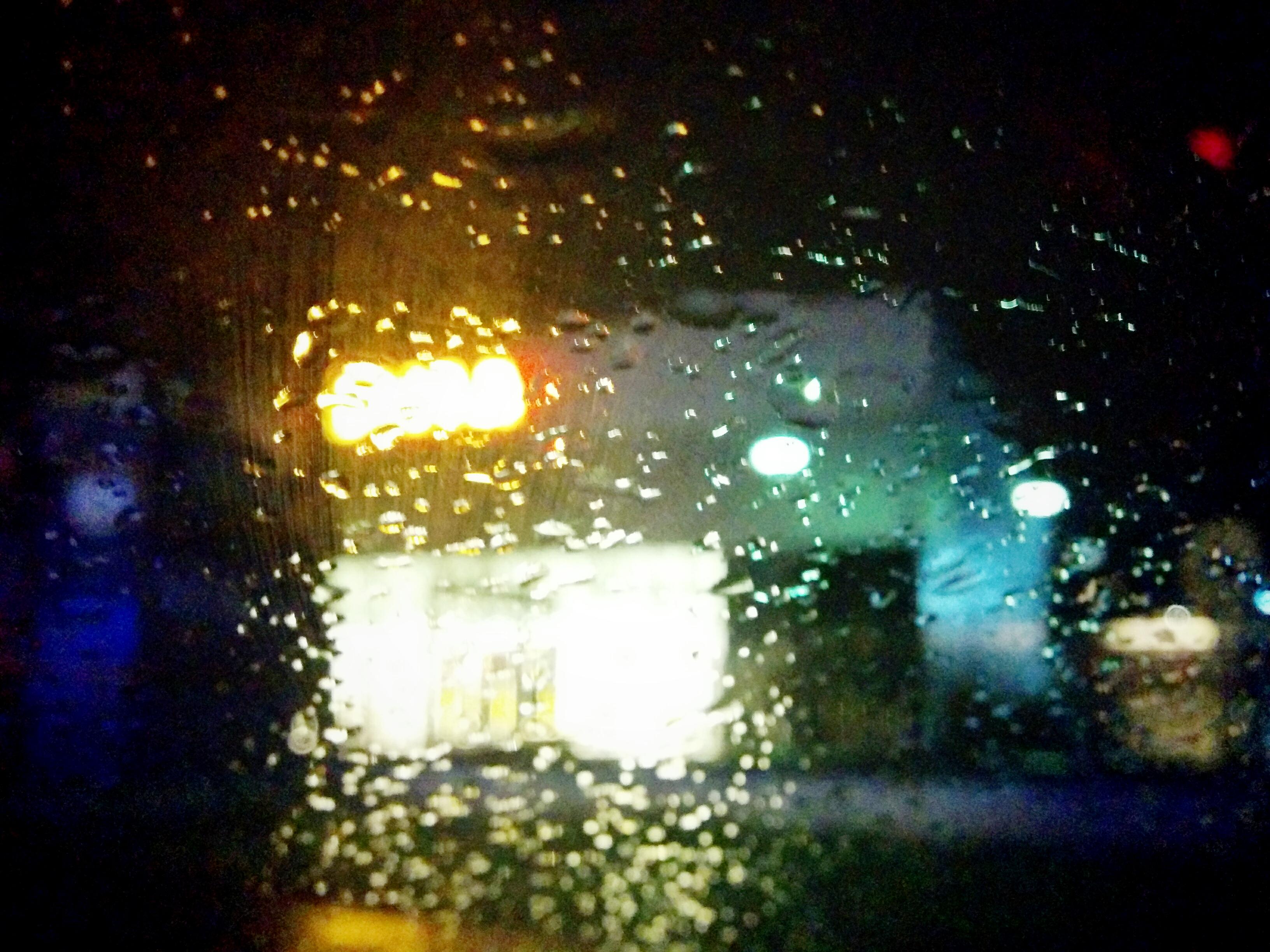 Čelní sklo auta v dešti před nákupním centrem.