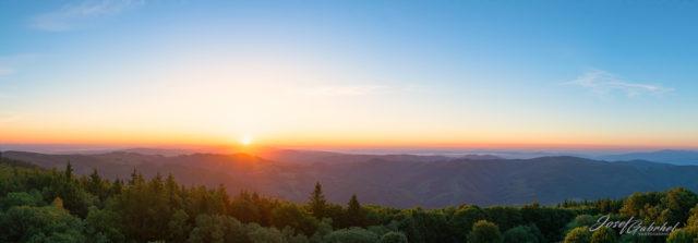 Fotka krajiny, které dominuje východ slunce.