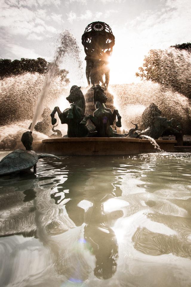 Fotografie fontány s odrazem ve vodě.