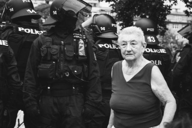 Reportážní fotografie: důchodkyně procházející demonstrací