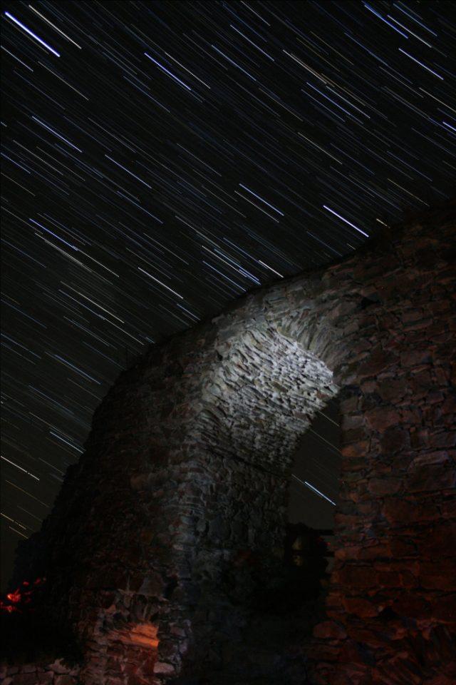 Jak fotit star trails: hvězdy nad nasvícenou bránou.