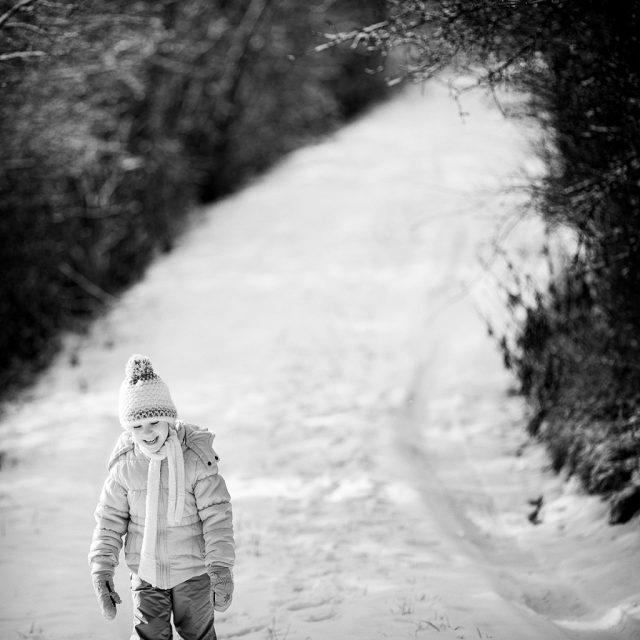 Zimní focení dětí: dítě na zasněžené cestě.