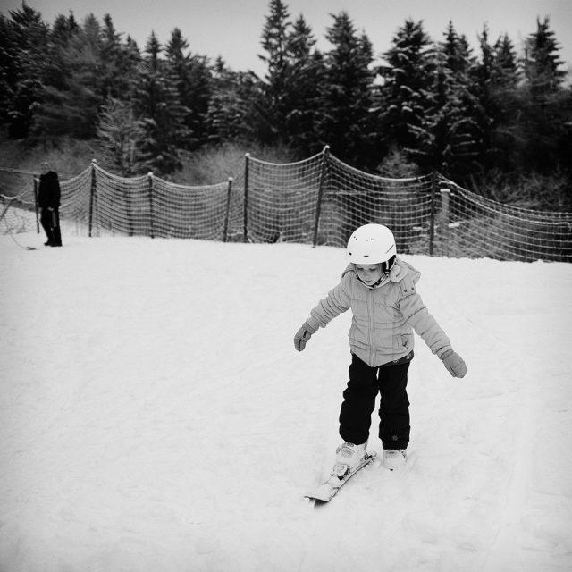 Zimní focení dětí: dítě poprvé na lyžích.