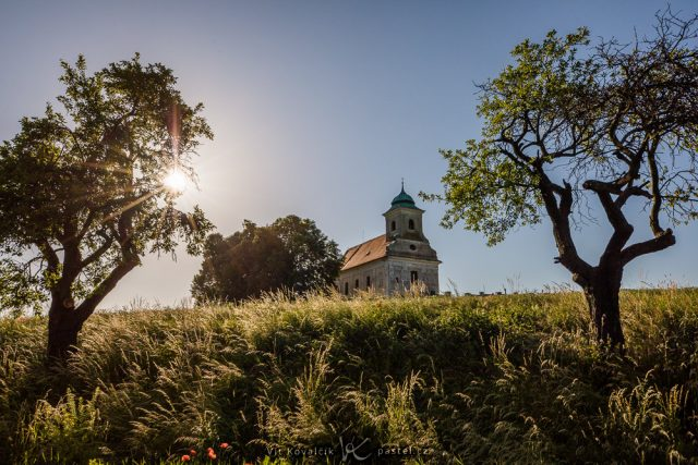 Jak vylepšit kompozici fotografie: širší záběr kapličky orámované stromy.