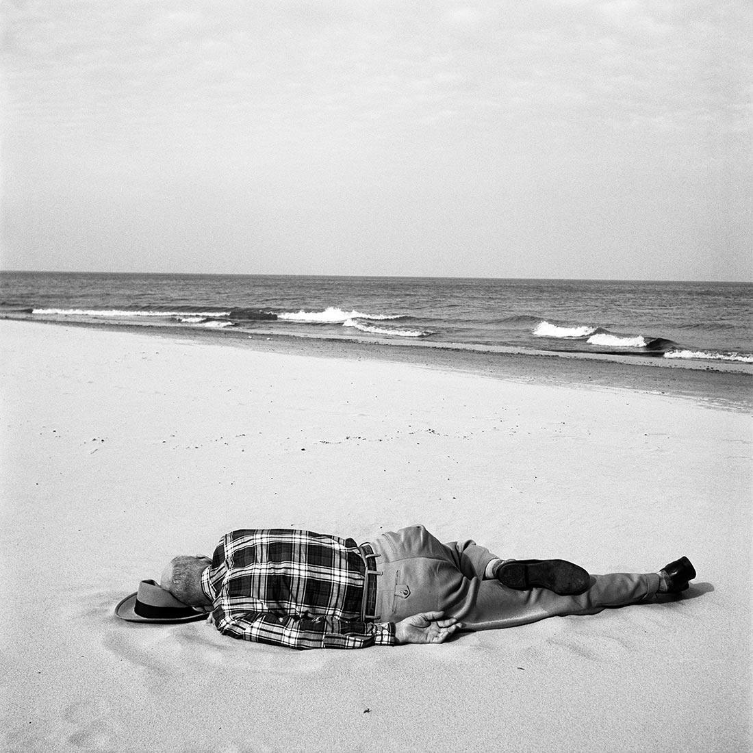 8 tipů od Vivian Maier – oblečený muž ležící na pláži
